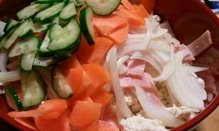 にんじん、きゅうり、たまねぎ、ベーコンともめん豆腐を投入。